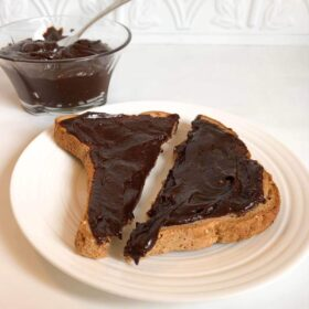 A glass dish full of chocolate spread next to some toast.