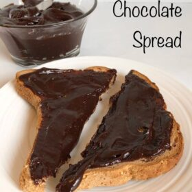 Toast slathered in chocolate spread on a white plate.