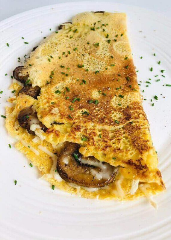 An omelette stuffed with mushrooms on a plate.
