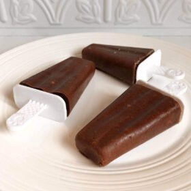 Three popsicles on a plate.