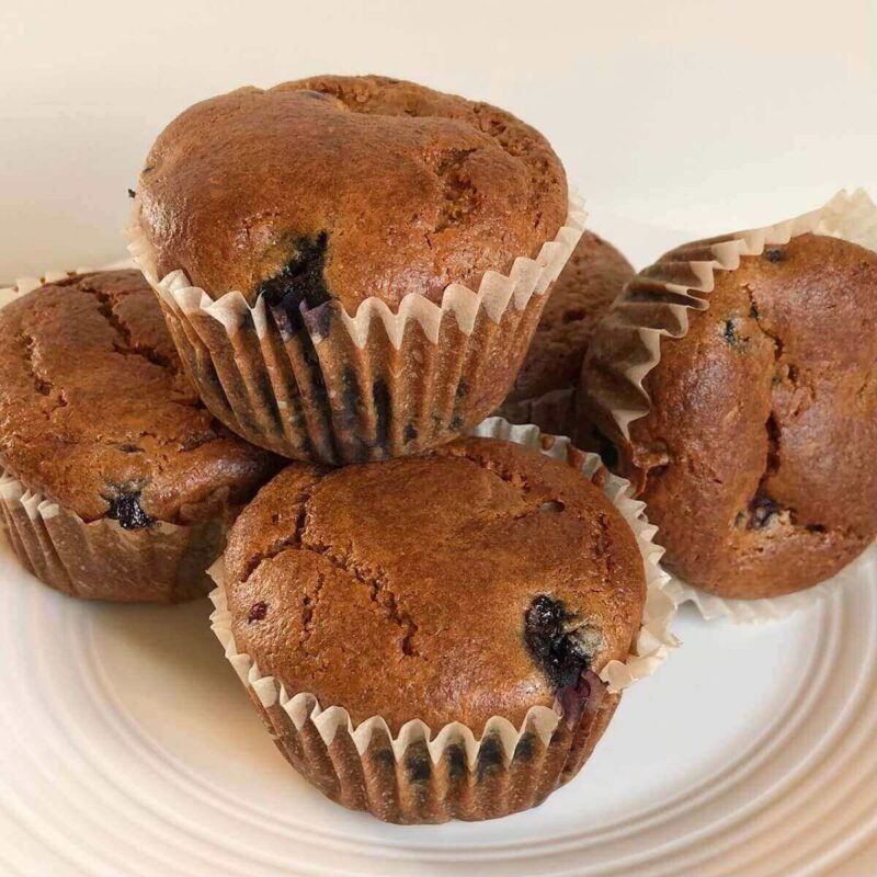 Five muffins displayed on a plate.