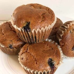 Muffins stacked and arranged on a plate.