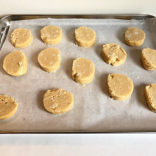 Raw cookie batter in slices on a sheet pan.