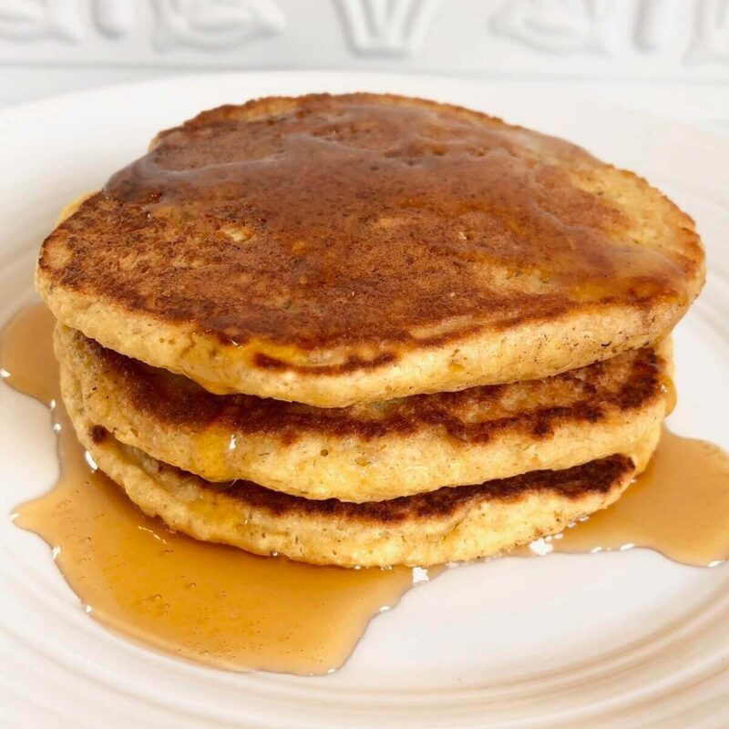 Oat flour pancakes stacked on a plate.