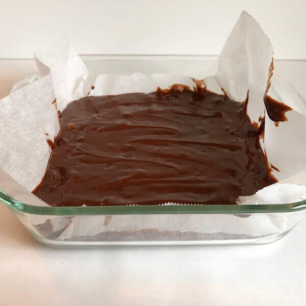 Raw brownie batter in a glass baking dish.
