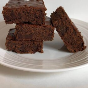 Brownies arranged on a white plate.