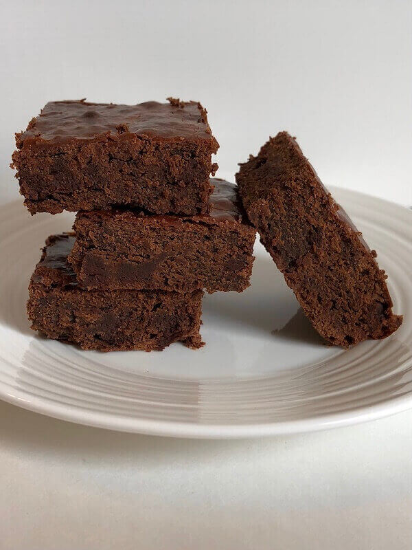 Brownies stacked on a white plate.