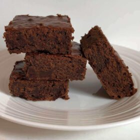 Four brownies on a plate.