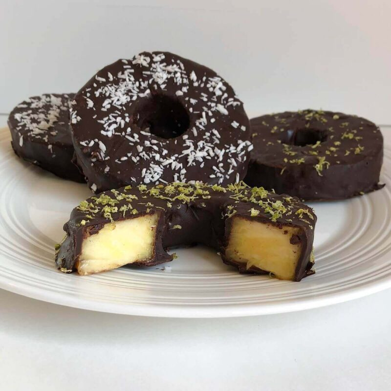 Four pineapple rings covered in chocolate.