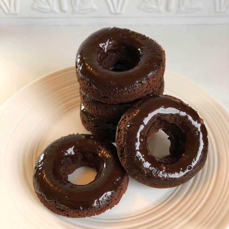 Donuts stacked on a plate.