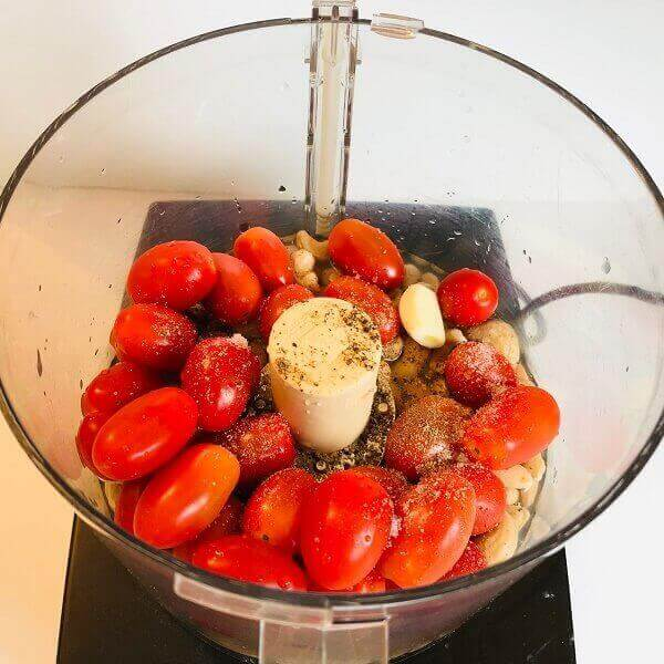 Tomatoes, cashews, and garlic in a food processor.