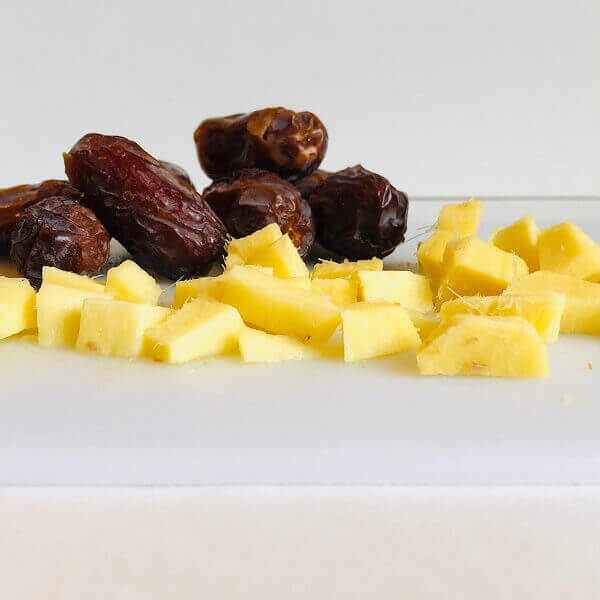 Dates and chopped ginger on a cutting board.