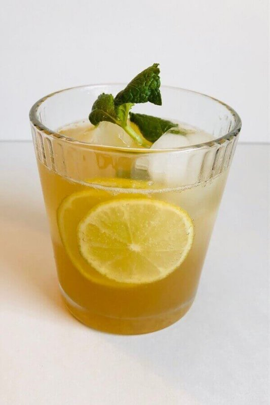 Ginger ale garnished with lime slices and a sprig of mint.