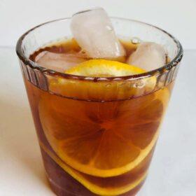 Iced tea in a glass with lemon.
