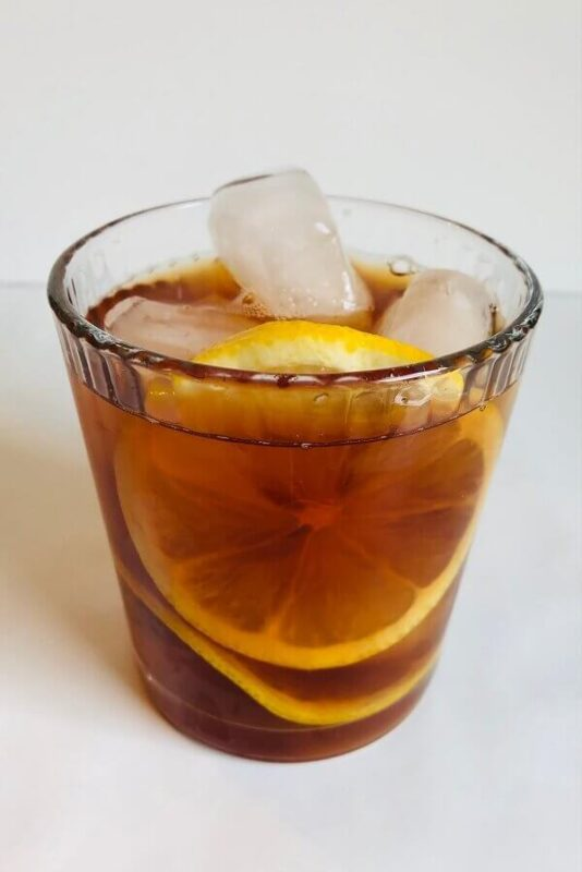 Iced tea in a glass with ice cubes and lemon slices.