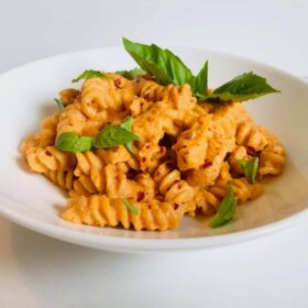 Pasta in a white bowl garnished with basil and crushed red pepper.