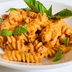 Pasta in a white bowl with fresh basil on top.