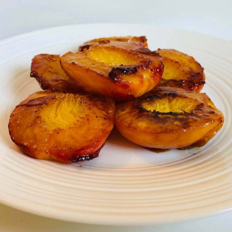 Cooked peach halves on a white plate.