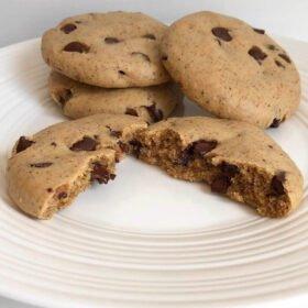 A cookie broken in half with three more cookies behind it.