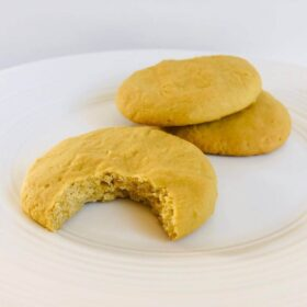 Three cookies on a plate with a bite missing from one.
