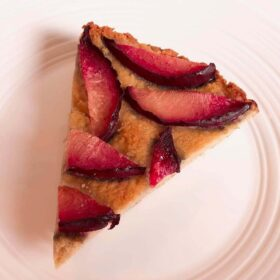 A piece of cake with sliced plums on top.