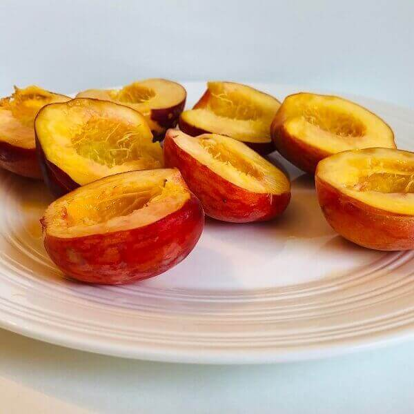 Raw fresh peach halves on a plate.