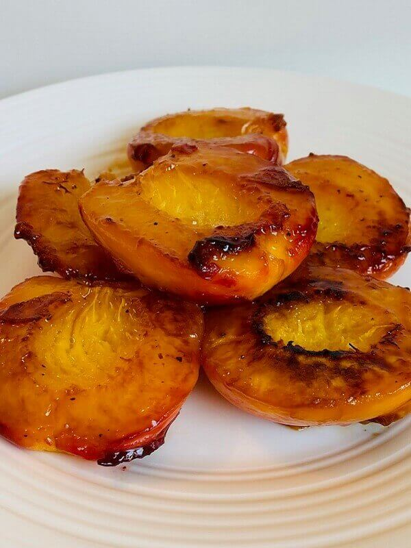 Six cooked peach halves on a white plate.