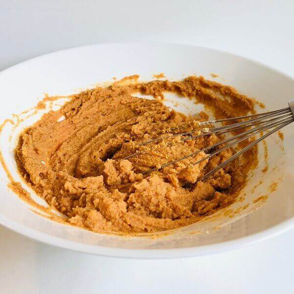 Raw pumpkin bread batter in a mixing bowl with a whisk.