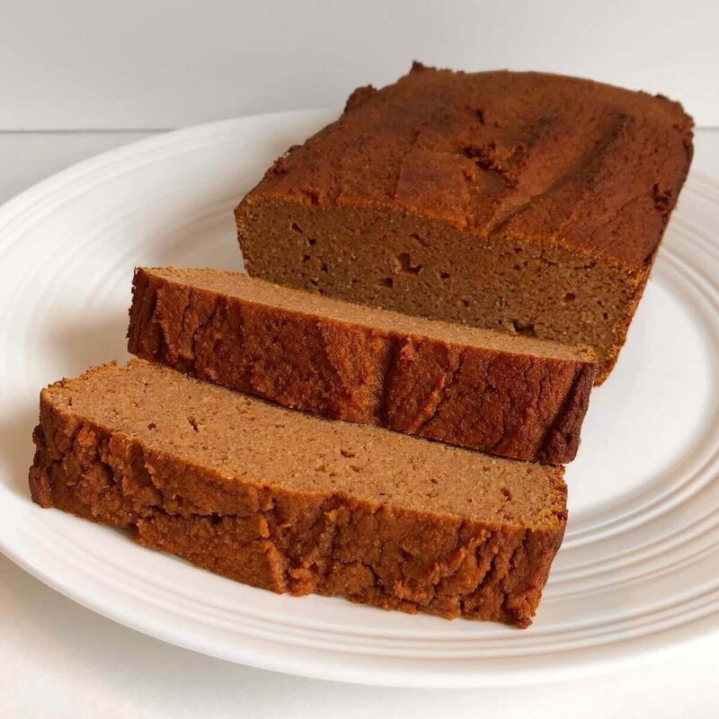 Pumpkin bread loaf and two slices on a white plate.