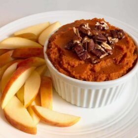A dish filled with hummus next to a pile of sliced apples.
